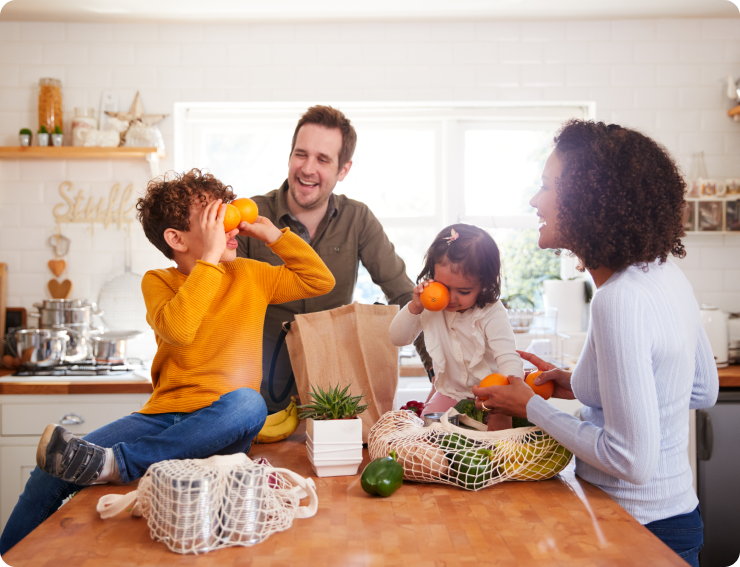Children with Oranges, Mom, dad, and two children in the kitchen unpacking grocery bags together