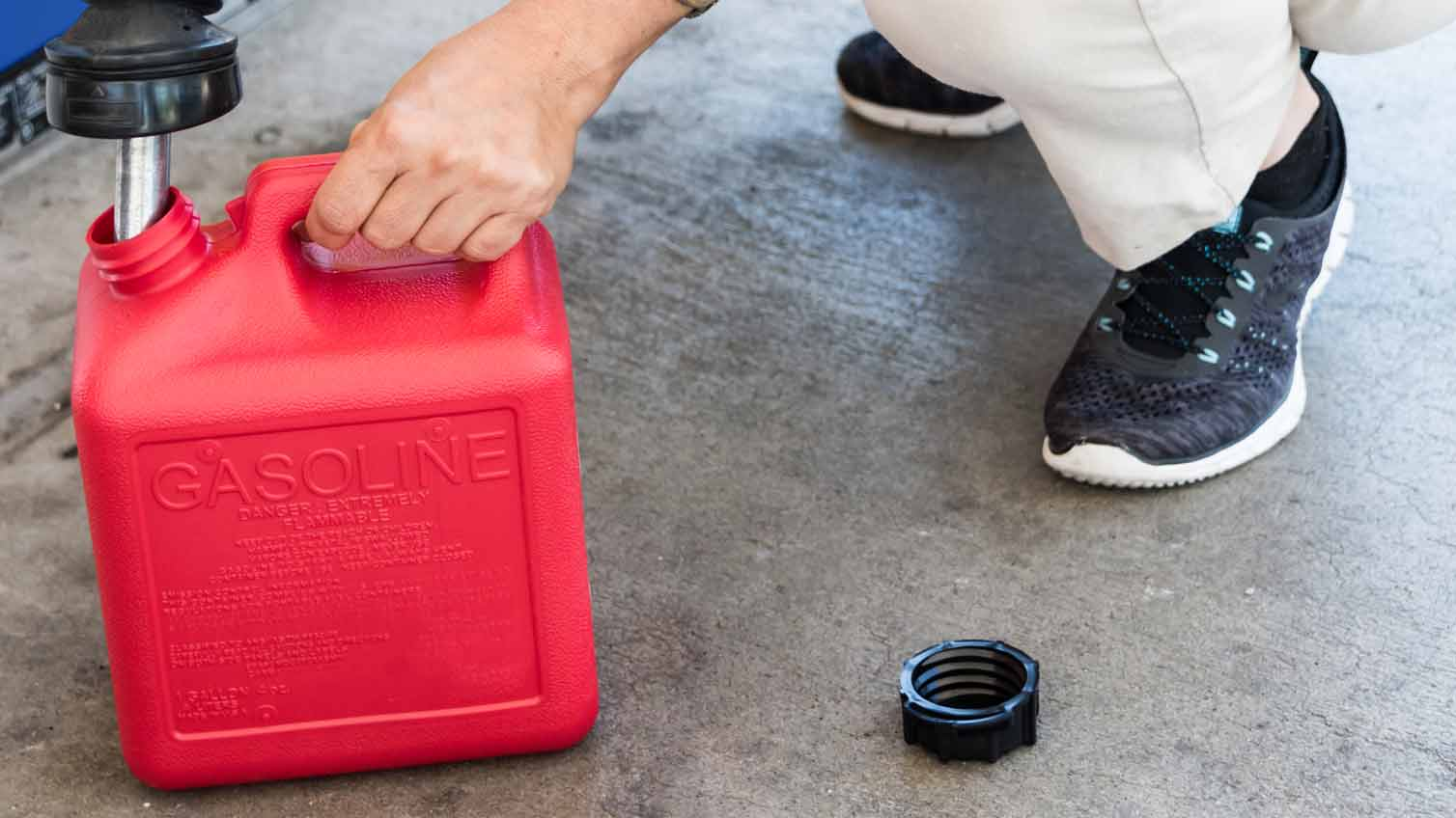 Person filling up a gas can on the ground.